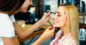 Makeup artist applying liquid tonal foundation on the face of the woman in make up room. Makeup artist applying liquid tonal foundation on the face of the woman Royalty Free Stock Image