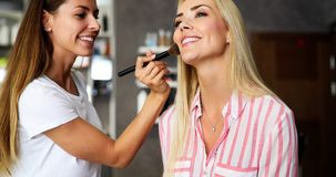 Makeup artist applying liquid tonal foundation on the face of the woman in make up room. Makeup artist applying liquid tonal foundation on the face of the woman Royalty Free Stock Photography