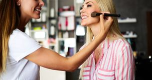 Makeup artist applying liquid tonal foundation on the face of the woman in make up room. Makeup artist applying liquid tonal foundation on the face of the woman Stock Photography