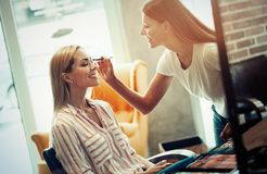 Makeup artist applying liquid tonal foundation on the face of the woman in make up room. Makeup artist applying liquid tonal foundation on the face of the woman Royalty Free Stock Photos