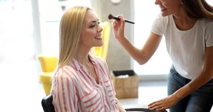 Makeup artist applying liquid tonal foundation on the face of the woman in make up room. Makeup artist applying liquid tonal foundation on the face of the woman Stock Photos