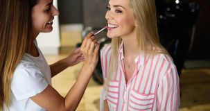 Makeup artist applying liquid tonal foundation on the face of the woman in make up room. Makeup artist applying liquid tonal foundation on the face of the woman Stock Photo