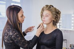 Makeup artist applying liquid tonal foundation on the face of the woman Royalty Free Stock Image