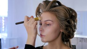 Makeup artist applying liquid tonal foundation on woman`s face Stock Image