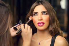 Makeup artist applying make up on beautiful model Royalty Free Stock Photos