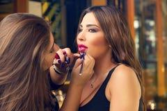 Makeup artist applying make up on beautiful model stock images