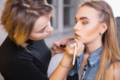 Makeup artist applying make up on gorgeous model stock image