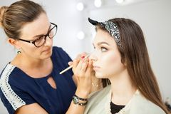 Makeup artist applying make up on model Royalty Free Stock Photos
