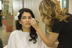 Makeup artist applying makeup for beautiful middle aged woman Royalty Free Stock Photos
