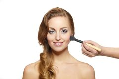 Makeup artist applying  makeup to attractive girl Royalty Free Stock Images
