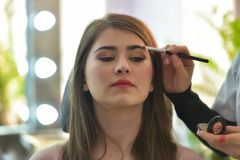 Makeup artist applying makeup to model in beauty salon Stock Images