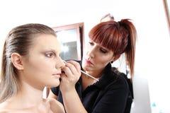 Makeup artist applying mascara on eyes Stock Photography