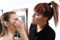 Makeup artist applying mascara on eyes of model Stock Photos