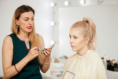 Makeup artist applying mascara to a blonde model Stock Images