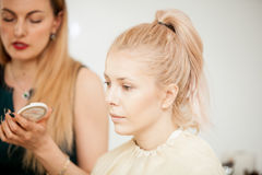 Makeup artist applying mascara to a blonde model Stock Photography