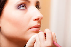 Makeup artist applying with pencil cosmetic on lips of woman Stock Photography
