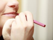 Makeup artist applying with pencil cosmetic on lips of woman Royalty Free Stock Images