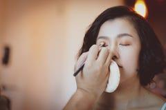 Makeup artist applying pink eyeshadow to beautiful Asian model stock photos