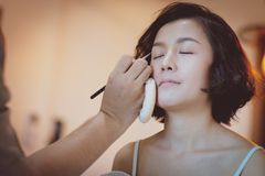 Makeup artist applying pink eyeshadow to beautiful Asian model stock photography