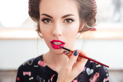 Makeup artist applying pink lipstick and brush to young woman Royalty Free Stock Images
