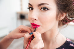 Makeup artist applying pink lipstick to lips of woman. Makeup artist applying bright pink lipstick to lips of young woman in curlers Stock Photos