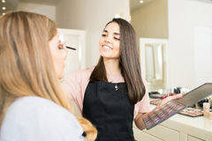 Makeup artist applying some eyeshadow. Wide view of a pretty brunette working as a make-up artist and putting some eyeshadow on a woman Stock Image