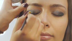 Makeup artist backstage. Closeup shot of makeup artist applying eyeshadows with brush on upper eyelid of smiling young brown haired female. Slow motion stock footage