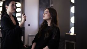 Makeup artist with black pony tail uses a make up finishing spray and gently sprays it on her client`s face from a. Distance. Gorgeous young lady in black dress stock video footage