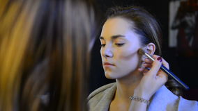 Makeup artist Blush dark blushes on brown long-haired model in studio stock video footage