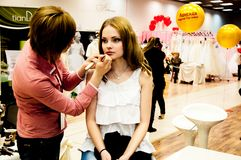 Makeup artist bring girl make-up Stock Photography