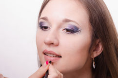 Makeup artist brings lip pencil client Royalty Free Stock Image