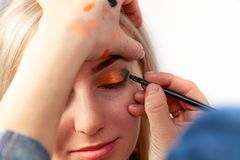 Makeup artist with a brush in the hands with a flat edge paints the arrow on the eyelid of the model, applies make-up to the eyes royalty free stock photo