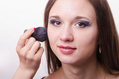 Makeup artist brush powder on face causes model. Makeup artist brush powder gets on the face of a beautiful young girl in the makeup Royalty Free Stock Image