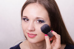 Makeup artist brush powders face of a beautiful girl Royalty Free Stock Photo