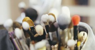 Makeup Artist Brushes Behind the Scenes of Fashion Show stock video footage
