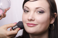 Makeup artist deals powder on the face model Stock Photo