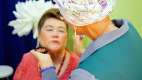 Makeup Artist do Age Maquillage for Senior Woman. Lifting Make Up Technique for Old Caucasian Lady. Adult Female Stylist Applying Blush on Client Cheek with stock footage