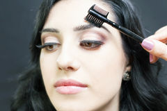 Makeup artist doing make up for beautiful arabian woman Royalty Free Stock Image