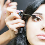 Makeup artist doing make up for beautiful arabian woman Royalty Free Stock Images