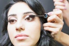 Makeup artist doing make up for beautiful arabian woman Royalty Free Stock Photo