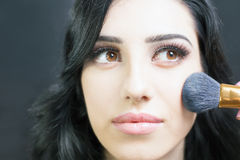 Makeup artist doing make up for pretty arabian woman Stock Photography