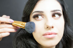 Makeup artist doing make up for pretty arabian woman Stock Image