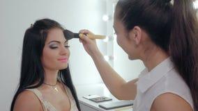 Makeup artist doing makeup. For the beautiful brunette. a makeup artist powders the face stock video footage