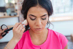 Makeup artist doing makeup to thoughtful pretty young woman Stock Photography