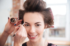 Makeup artist doing makeup to woman with curlers Royalty Free Stock Images