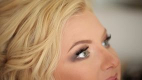 Makeup artist doing makeup. For young blonde caucasian woman stock video footage