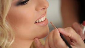 Makeup artist doing makeup. For young blonde caucasian woman stock footage