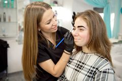 Makeup artist doing professional makeup of young woman near the mirror in beauty studio stock photography