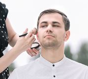 Makeup artist doing makeup for a young man. Lifestyle stock photography