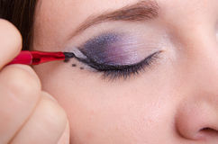 Makeup artist draws arrows on the eyelids model Royalty Free Stock Photo